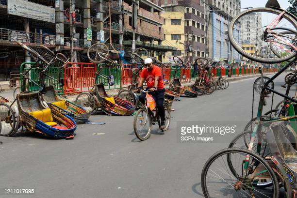 Man rides past a line of inverted rickshaws on the street during a nationwide lockdown. Due to the COVID-19 pandemic, Bangladesh Government...