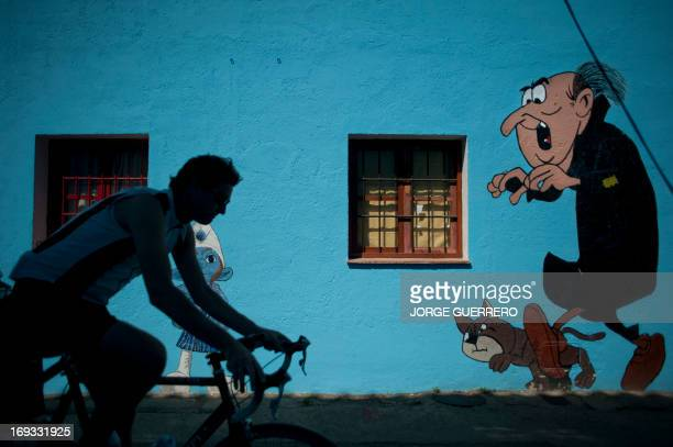 A man rides past a painting of Gargamel the Evil Wizard a character of the Smurfs in the village of Juzcar near Malaga southern Spain on May 23 2013...