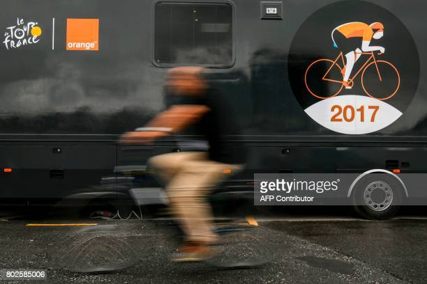 TOPSHOT A man rides past a truck bearing the logo of the Tour de France cycling race in Dusseldorf Germany on June 28 three days before the start of...
