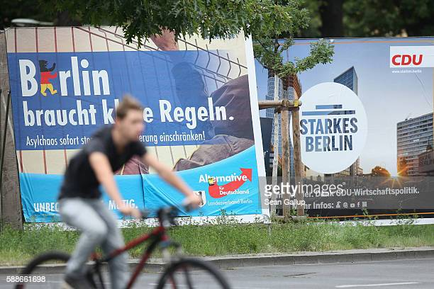 A man rides past election campaign billboard for the populist Alternative fuer Deutschland and the German Christian Democrats on August 12 2016 in...