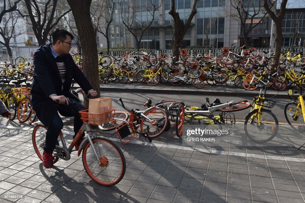 A man rides past shared bicycles piled beside a road in Beijing on February 21, 2018. China issued national guidelines governing bike-sharing operations in 2017 in an effort to nurture a new industry credited with spurring a transport revolution while addressing mounting complaints over an accumulation of millions of bikes on city streets. /