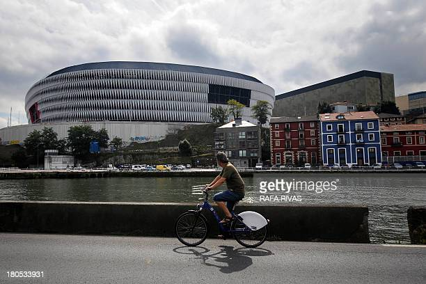 A man rides past the new San Mames football stadium in the Northern Spanish Basque city of Bilbao on September 14 2013 AFP PHOTO/ RAFA RIVAS