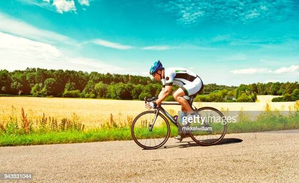 Man rides race bike on country road on a summer day