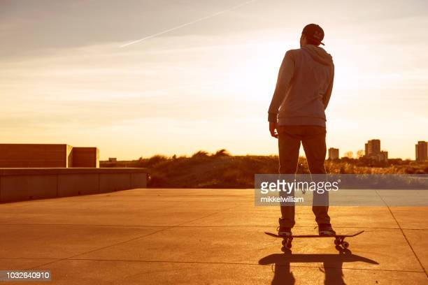 Man rides skateboard as the sun sets in the horizon