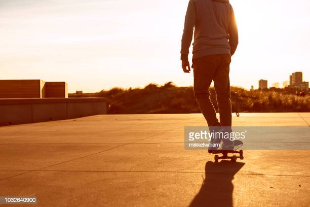 Man rides skateboard forward as the sun sets in the horizon