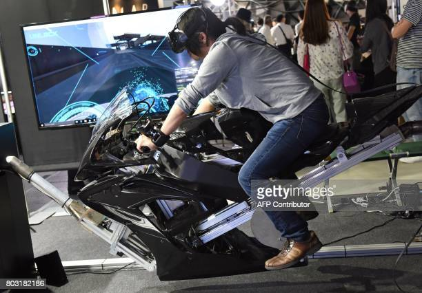 A man rides the 'GODSPEED VR airborne' transforming motorcycle simulator system presented by Japan's Prototype at the VR/AR World Exhibition as part...