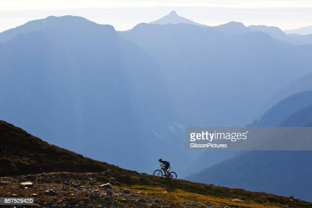 a man rides up a steep mountain bike trail in british columbia, canada. - steep stock photos and pictures