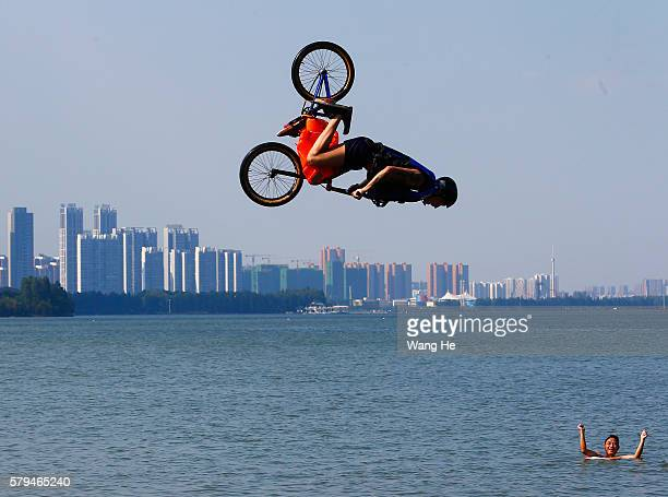 A man riding a bicycle falls into the East Lake in on July 24 2016 in Wuhan Hubei province China This activity which requires participants to ride...