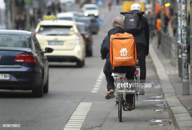 Man riding a bicycle for food delivery service Lieferando passes through an intersection on March 9, 2018 in Berlin, Germany. A variety of food...