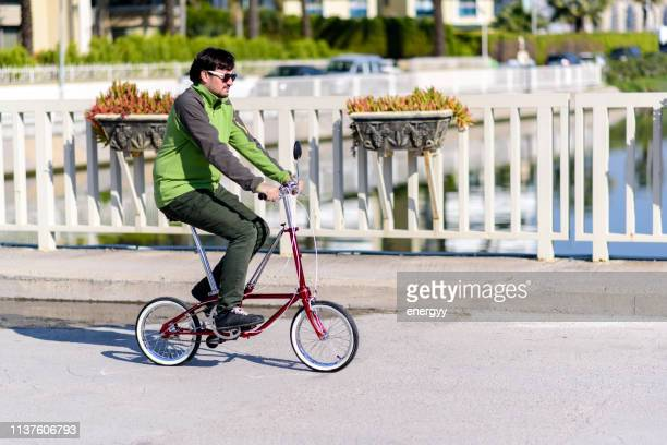 man riding a bicycle in the city - foldable stock pictures, royalty-free photos & images