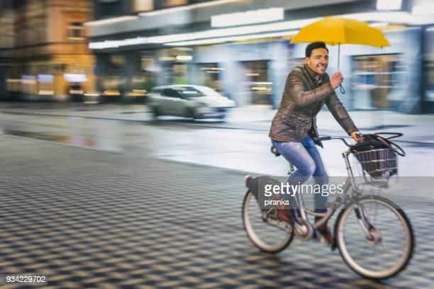 Man riding a bicycle on a rainy night