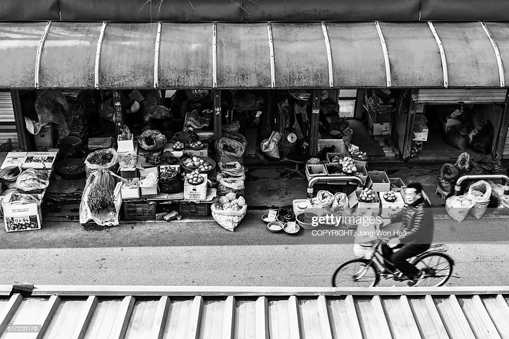 A man riding a bicycle on the road in the outdoor marketplace : Stock Photo