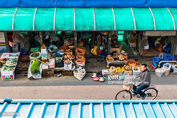 a man riding a bicycle on the road in the outdoor marketplace - jeonju stock photos and pictures