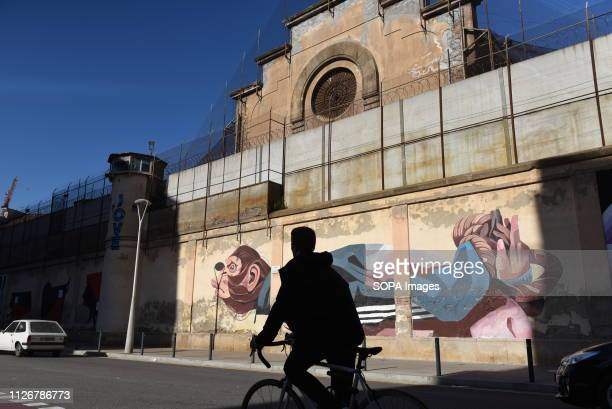 A man riding a bicycle pass front of a murals painting at 'La Modelo' prison in Barcelona