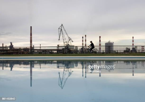 A man riding a bicycle past a Kobe Steel Ltd plant is reflected on a swimming pool in Kakogawa Hyogo Japan on Saturday Oct 14 2017 Kobe Steel's fake...
