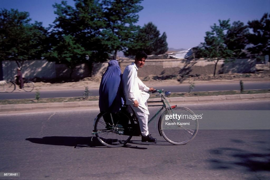 A man riding a bicycle with his burka-clad wife sitting on the back, Kabul, Afghanistan, 18th April 2002.