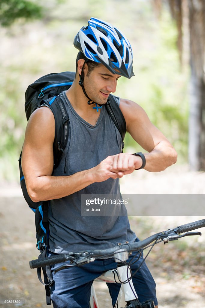 Man riding a bike and using a smart watch : Stock-Foto