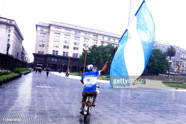 A man riding a bike waves an Argentine flag outside Casa Rosada on the day after the presidential elections on October 28 2019 in Buenos Aires...
