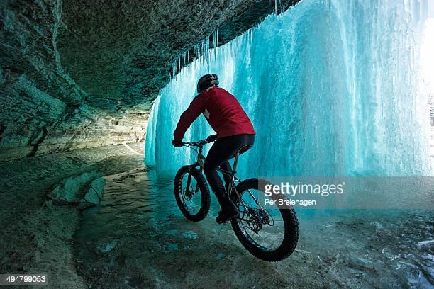 A man riding a fat bike behind a frozen waterfall