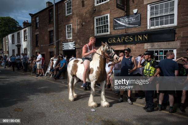 A man riding a horse has a conversation with a police officer outside a pub on the opening day of the annual Appleby Horse Fair in the town of...