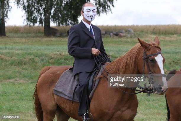 Man riding a horse wearing Guy Fawkes mask is seen in Grunwald Poland on 13 July 2018 Battle of Grunwald reenactment participants take part in the...