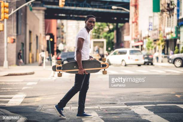 Man riding a longboard skateboard in New York City