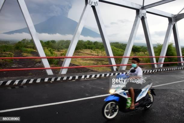 A man riding a motorcycle crossing a bridge on Jl Kubu Karangasem Bali on 27 November 2017 when the phreatic eruption of Mount Agung happened