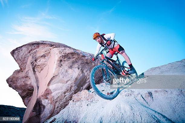 a man riding a mountain bike down a steep descent - robb reece stockfoto's en -beelden