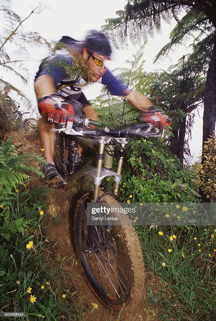 Man Riding a Mountain Bike on a Mud Track : Stock Photo
