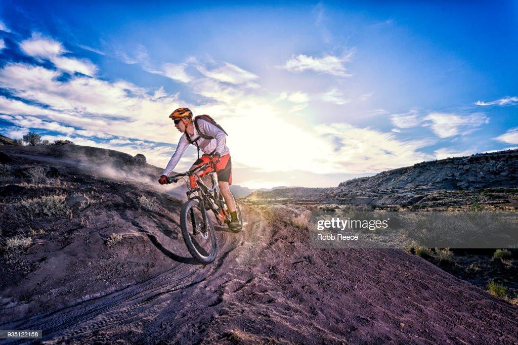 A man riding a mountain bike on an extreme dirt trail : Stock Photo