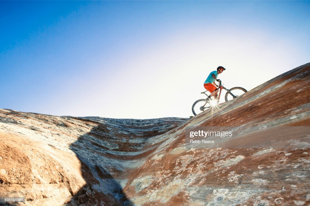 A man riding a mountain bike on an extreme sandstone ledge : Stock Photo