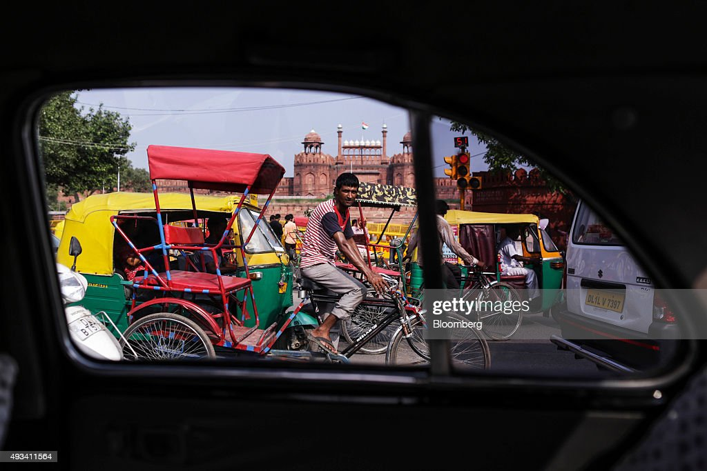 A man riding a rickshaw and an auto rickshaw passing the Red Fort are seen through the rear window of a Hindustan Motors Ltd. Ambassador taxi in New Delhi, India, on Saturday, Sept. 19, 2015. As cabs lured by app-based platforms proliferate in India, where car ownership is low and public transportation services in most cities and towns havent kept pace with the needs of a growing population, drivers are facing stiffer competition for rides. Photographer: Dhiraj Singh/Bloomberg via Getty Images