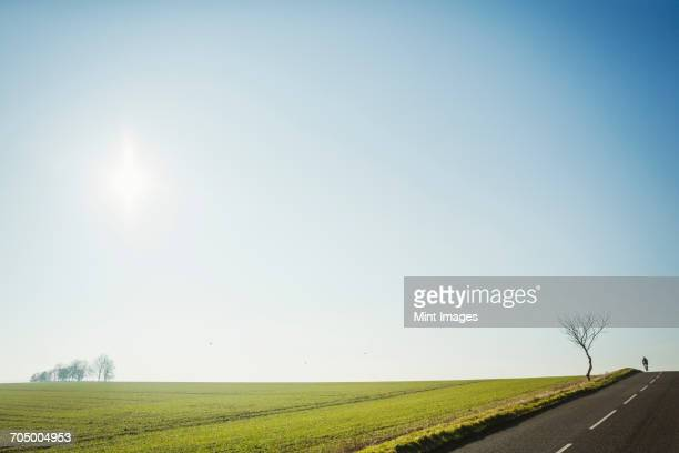a man riding a road bike on a country road, silhouette on the brow of a hill. disappearing into the distance.  - wielrennen stockfoto's en -beelden