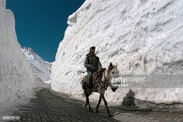 A man riding a steed passes through the snowcleared SrinagarLeh highway on April 30 2016 in Zojila 108 km east of Srinagar the summer capital of...