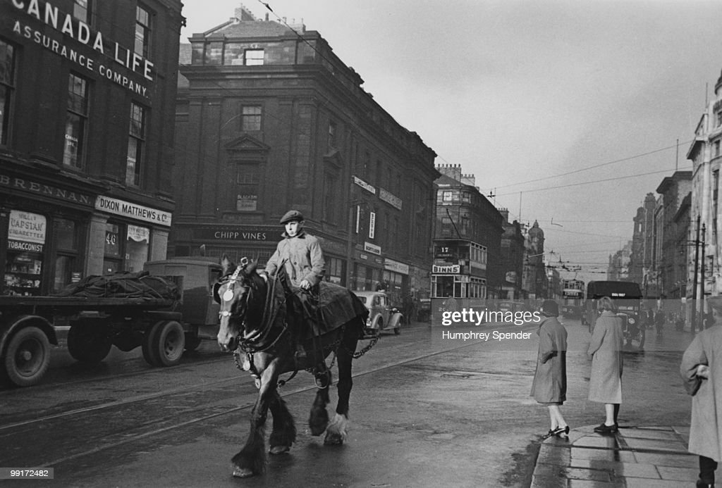 A man riding a workhorse down a street in Newcastle upon Tyne