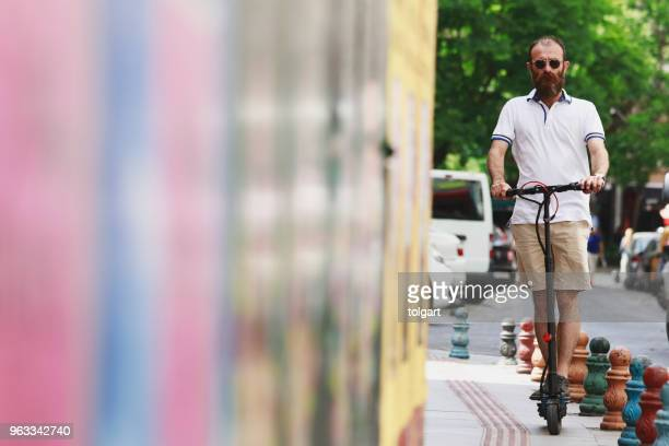 man riding an electric scooter - mobility scooter stock photos and pictures