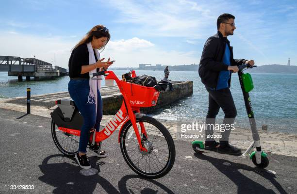 A man riding an escooter overtakes a woman pausing to check her cellphone while riding an UberJump electric bicycle on the Ciclovia Lisboa Cidade by...