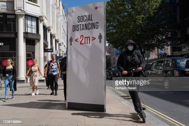 Man riding an eScooter speeds past a social distance board on Oxford Street during the Coronavirus pandemic, on 20th August 2020, in London, England.