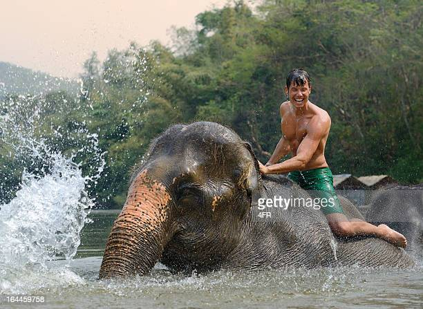 Man riding and bathing an Elephant, Tropical Rain Forest