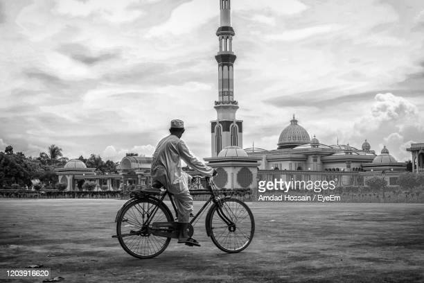 man riding bicycle against sky in city - amdad hossain stock pictures, royalty-free photos & images