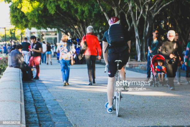 man riding bicycle by people on road - brisbane stock pictures, royalty-free photos & images