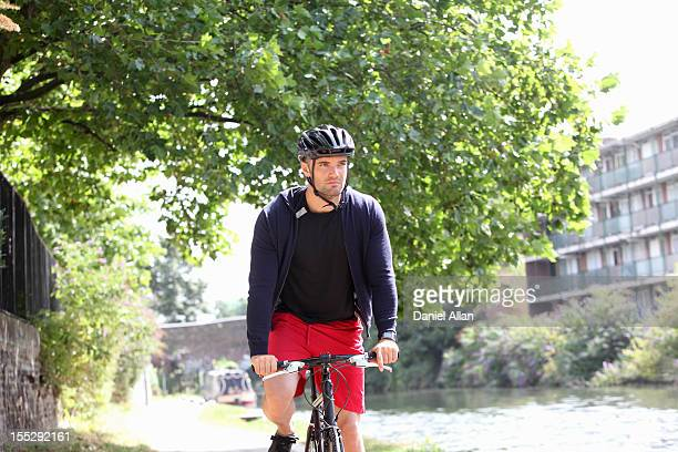 man riding bicycle by urban river - helmet stock pictures, royalty-free photos & images