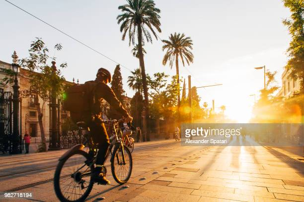 Man riding bicycle during sunset on the streets of Seville, Spain