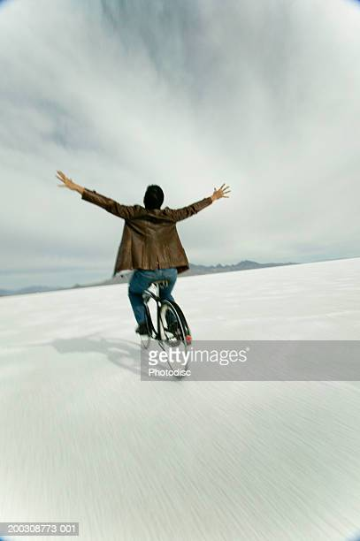 man riding bicycle hands free, in desert, elevated view - hands free cycling stock pictures, royalty-free photos & images