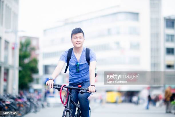 man riding bicycle in city - sigrid gombert stock-fotos und bilder