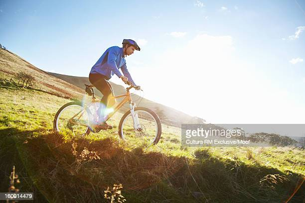 Man riding bicycle in grassy field
