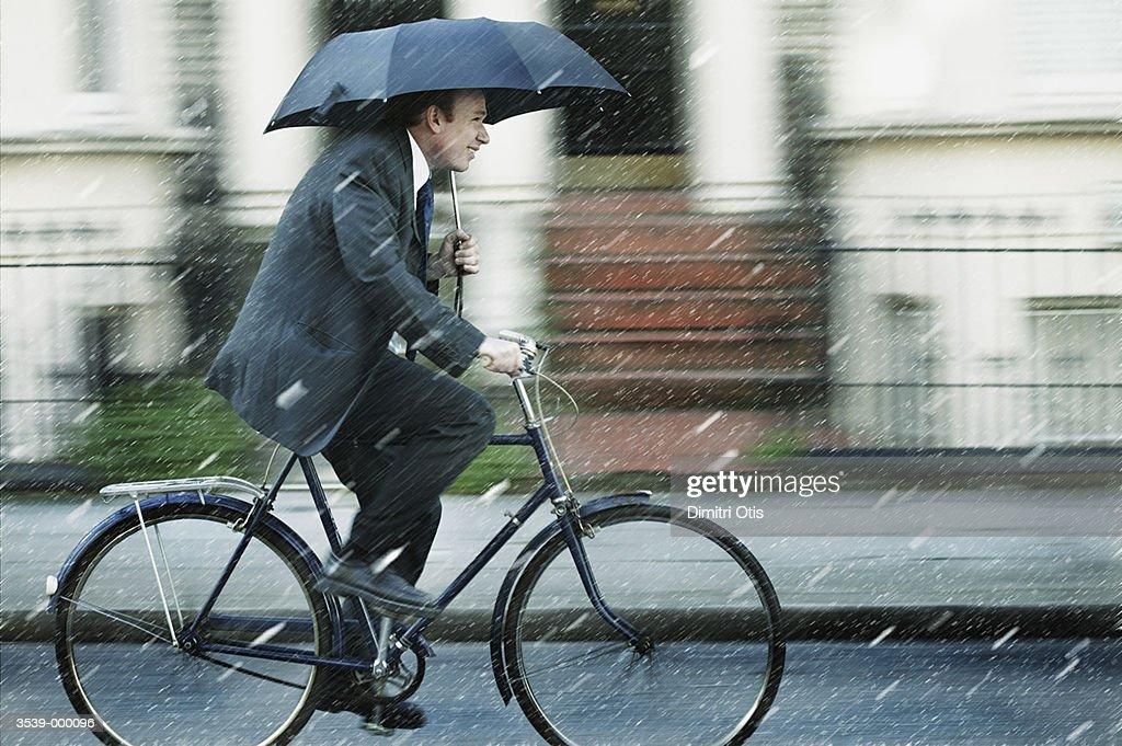 Man Riding Bicycle in Rain : Stock Photo