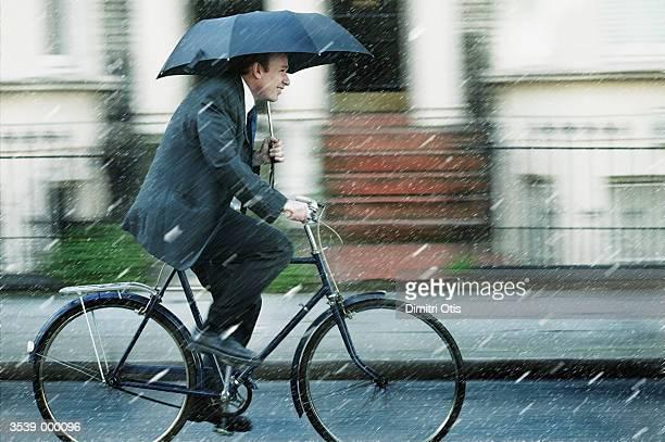 Man Riding Bicycle in Rain