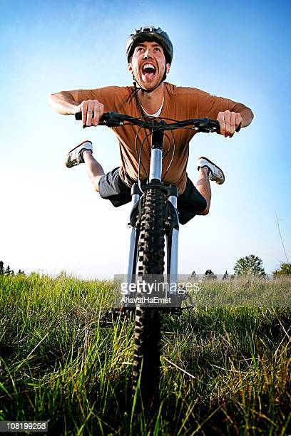 Man Riding Bicycle, Lying on Seat with Feet in Air