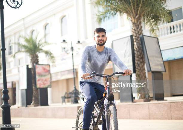 fit young man riding bicycle city